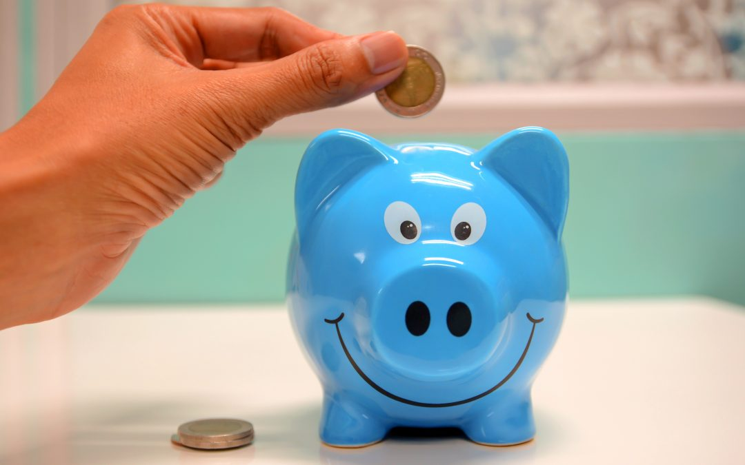 Hand Putting Coin In Blue Piggy Bank To Save Money For Travel