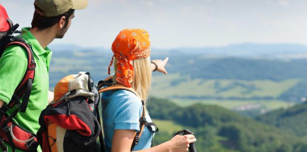 Female and Male Backpackers With Backpacks On Their Backs Looking And Pointing At Scenery While Living Working Playing and Travelling Around The World.