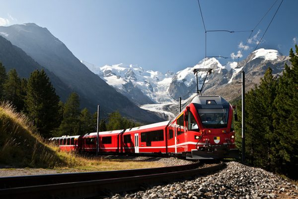 Red Train On Track Coming Through Snow Capped Mountains in Europe