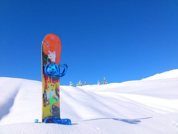 Colourful Snowboard Left Standing In The Snow While Skiing