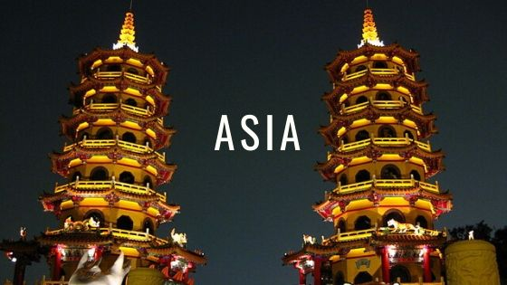 Two Pagodas lit Up With Golden Light At Night With The Word Asia.