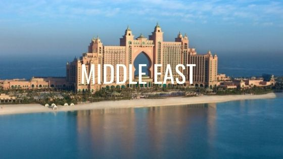 Large Sandstone Hotel Surrounded By Water in Dubai With The Words Middle East.