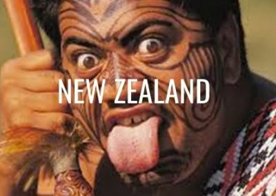 Maori With A Tattoos On His Face And His Tongue Poking Out With The Words New Zealand.