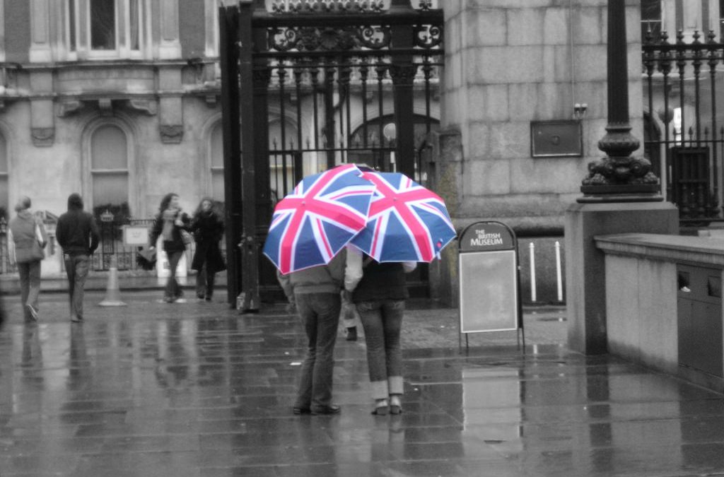 Man And Woman Standing In Front Of The British Museum With A British Flag Umbrella As It Is Raining.