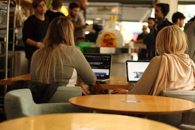 Two Females Sitting In A Cafe Using Free WiFi.