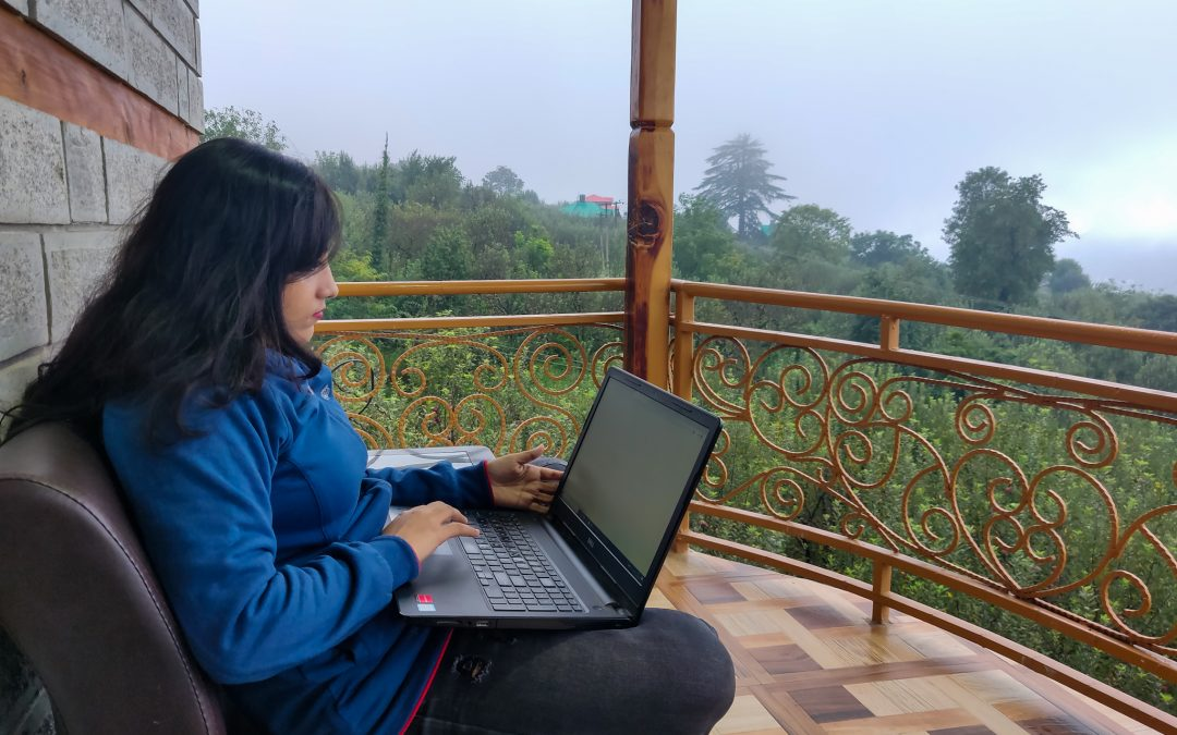 Rachita Saxena working remotely on her laptop with a view