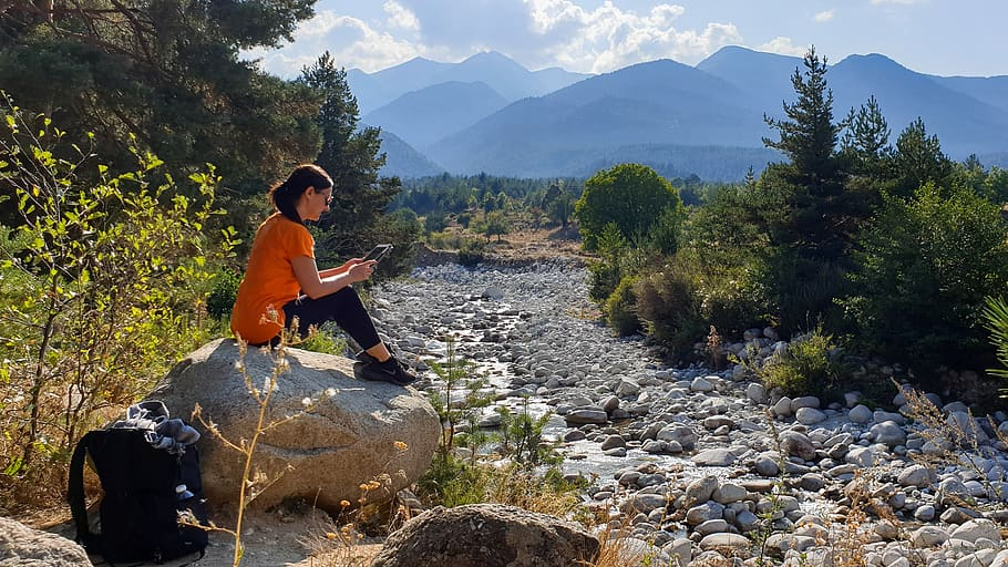 Female Sitting On A Bank Beside A River