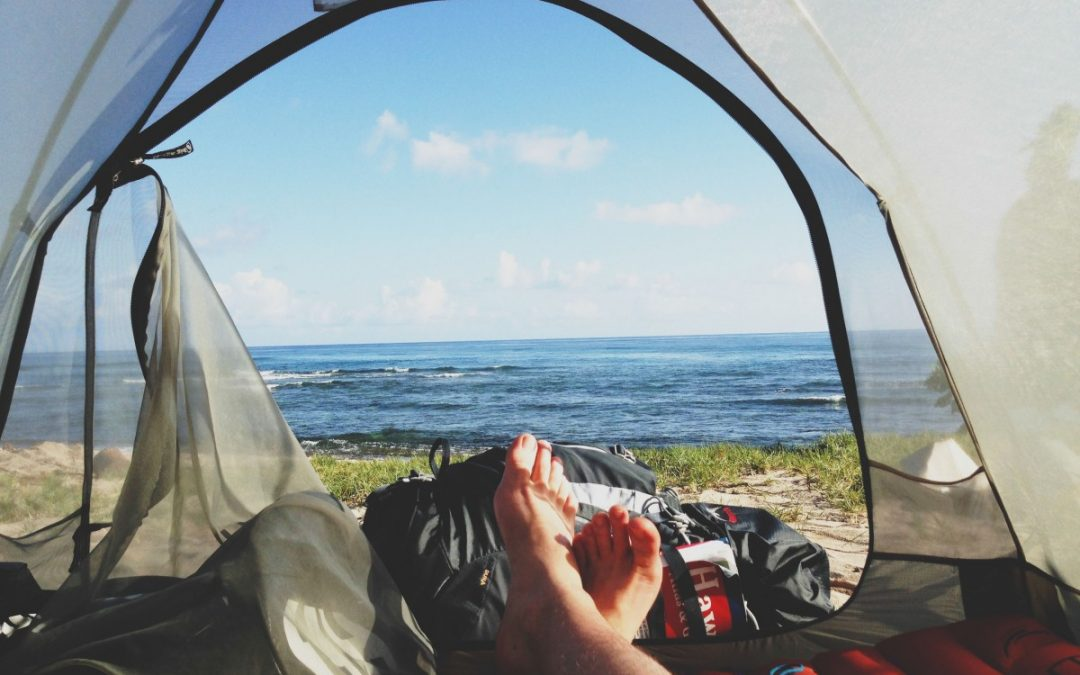 A Person Lying In A Tent With The Door Open With A View Over To The Ocean.