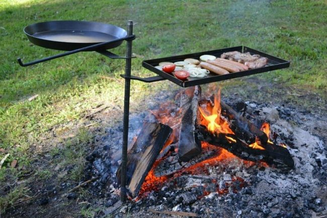 Camping Cooking Stand With Fry Pan And Flat Grill With Sausages and Onion Cooking Over An Open Fire.