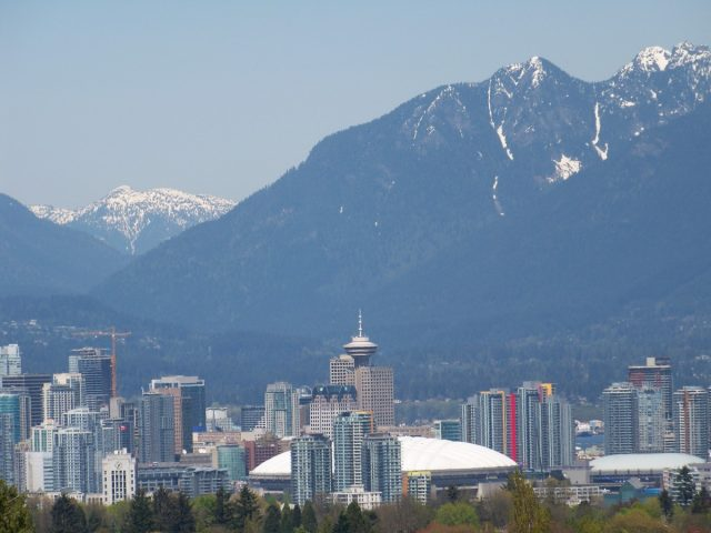 Downtown Vancouver With Snow Capped Mountains Behind.