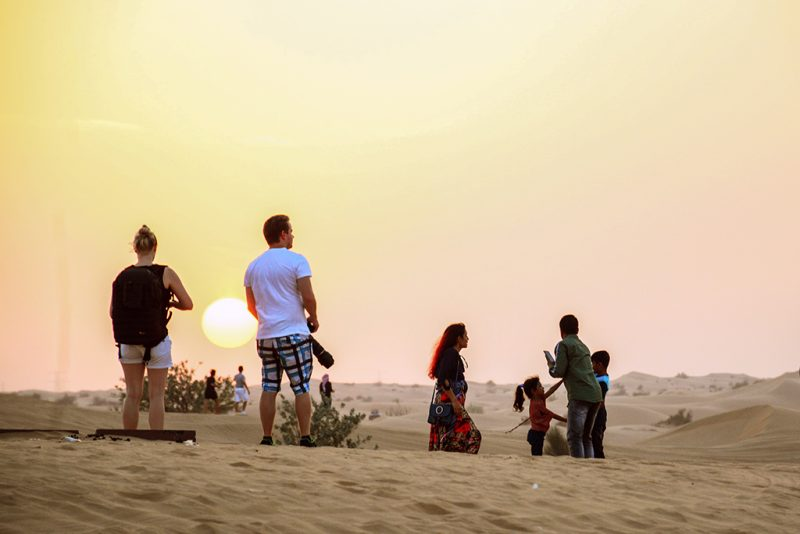 People Standing In The Dubai Desert Taking Photos Of The Sunset.