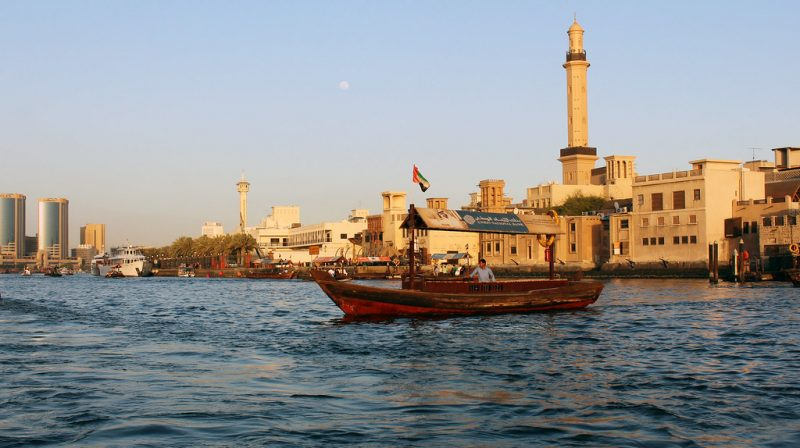 Person In Their Boat On The Water With Old Dubai Behind.