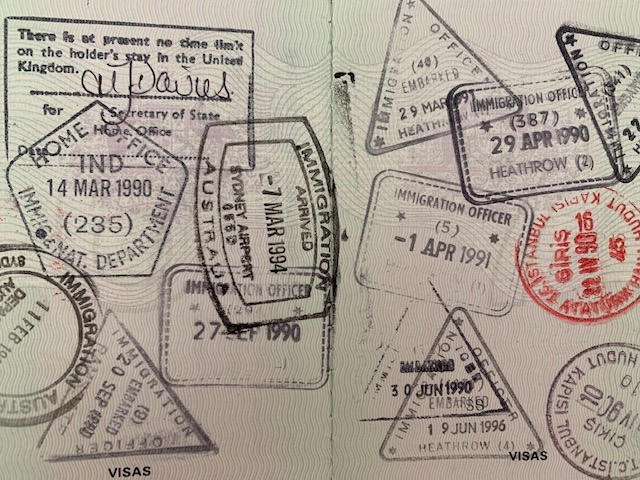 Black And Red Visa Stamps On Two Pages Of A Passport.