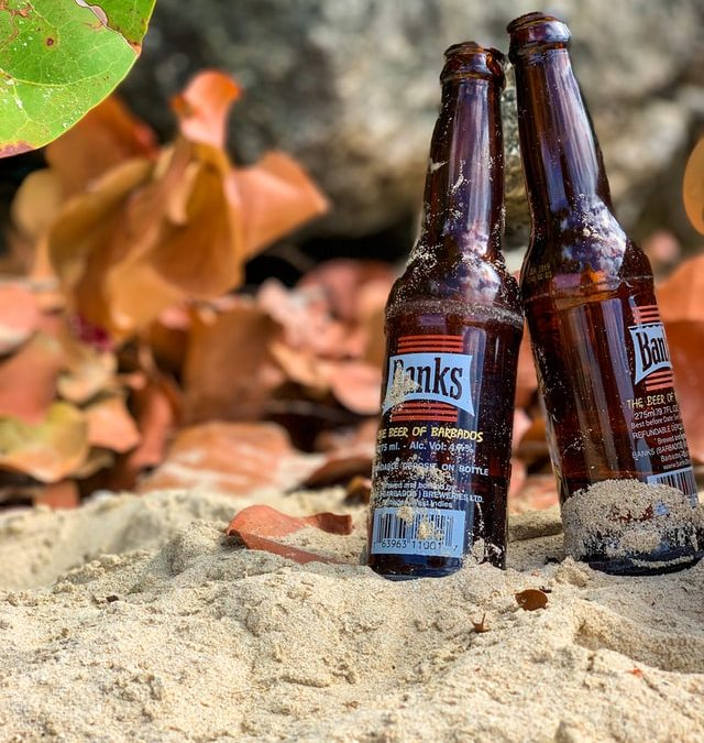 Barbados Beer Bottles On A Sandy Caribbean Beach.