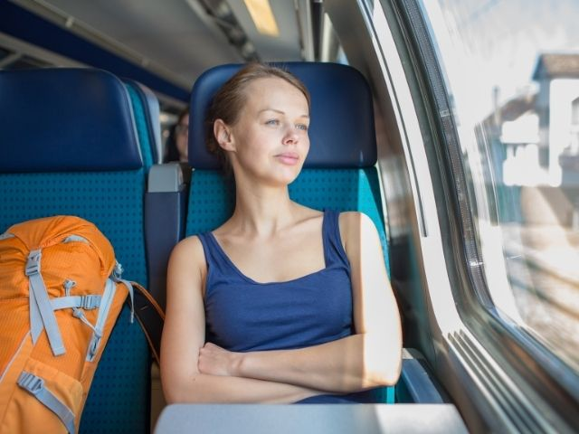 Female Sitting On A Blue Seat Of A Train With An Orange Backpack Next To Her And Looking Out Of The Window.