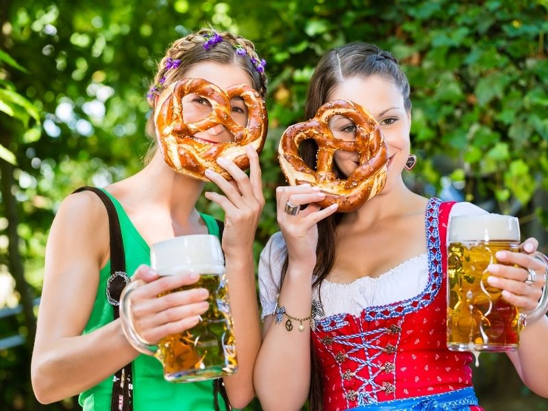 Girls In Traditional German Dress With A Styne Of Beer And A Pretzel.