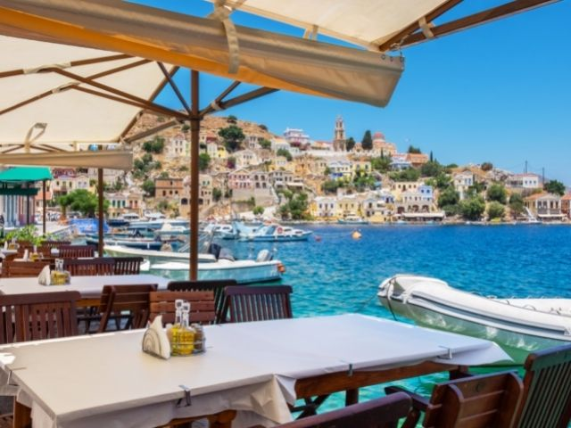 Greek Island Restaurant By The Water. Sitting Right On The Water Overlooking Crystal Blue Water Enjoying The Harbour.