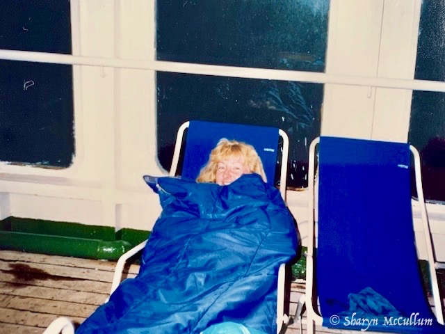 Sharyn McCullum In A Sleeping Bag In A Blue Chair On The Deck Of A Ferry On The Way To Crete, One Of The Greek Islands.