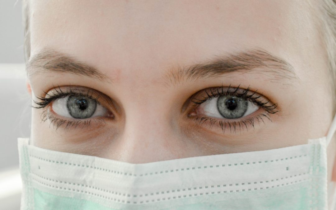 Female's Face With A Blue Face Mask To Protect Herself During The Pandemic.