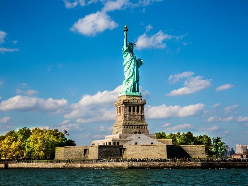 State Of Liberty On A Sunny Blue Sky Day Standing On Ellis Island, New York.