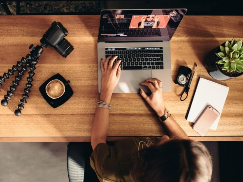 Female Digital Nomad Sitting At Her Desk With Her Laptop And Photo Equipment.