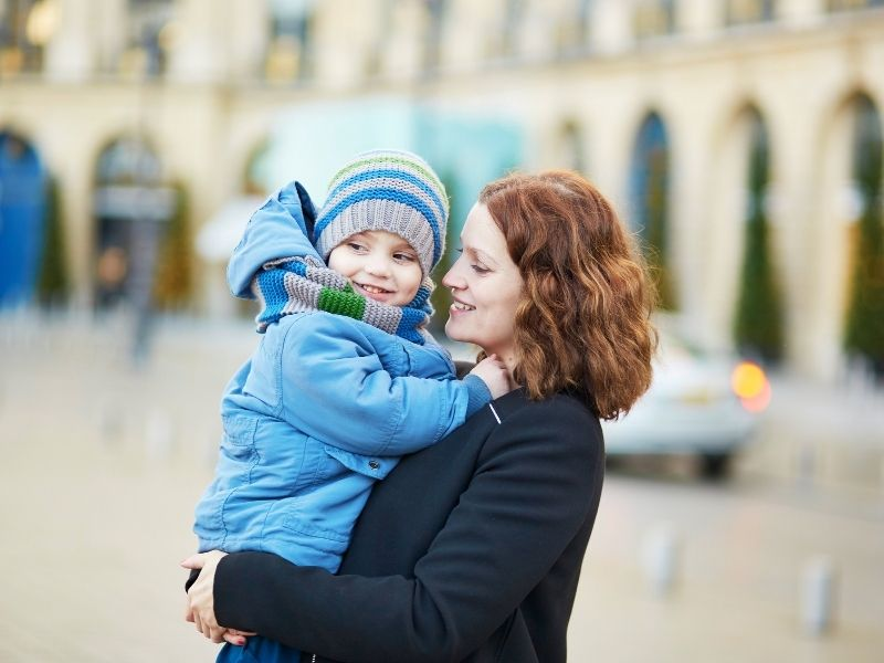 Being An Au Pair In France Involves Looking After Children. This Child In Her Blue Parka Enjoys Being Held By Her Au Pair.