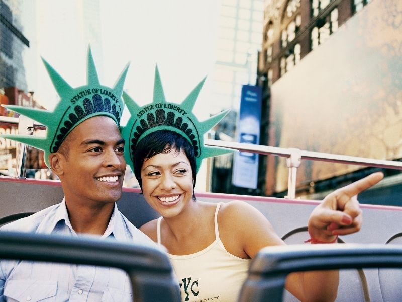 Two People On A Open Top Tour Bus In New York. They Bought Their Tour On GetYourGuide.