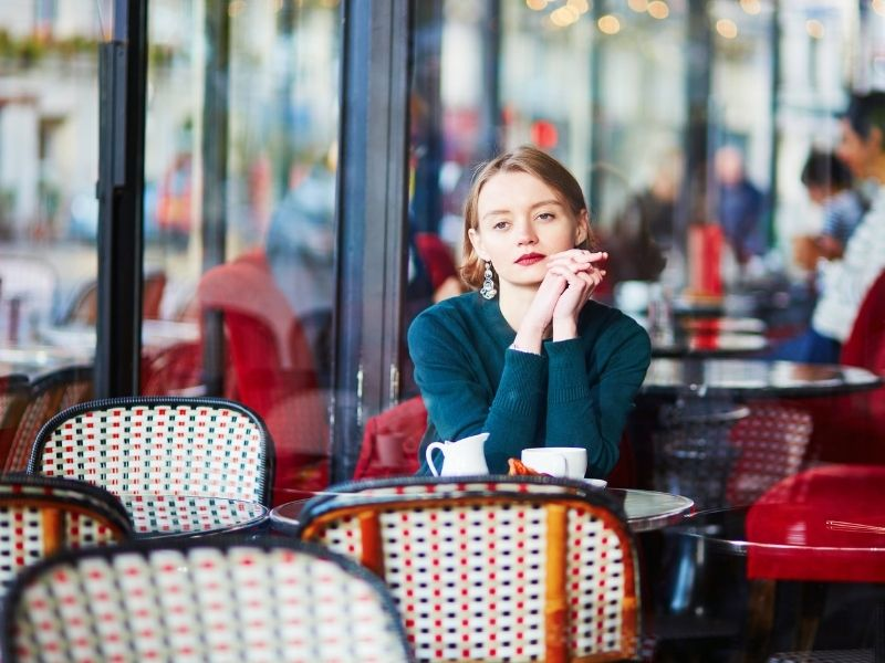 Female Sitting Alone In A Paris Cafe After Arriving On A Working Holiday.