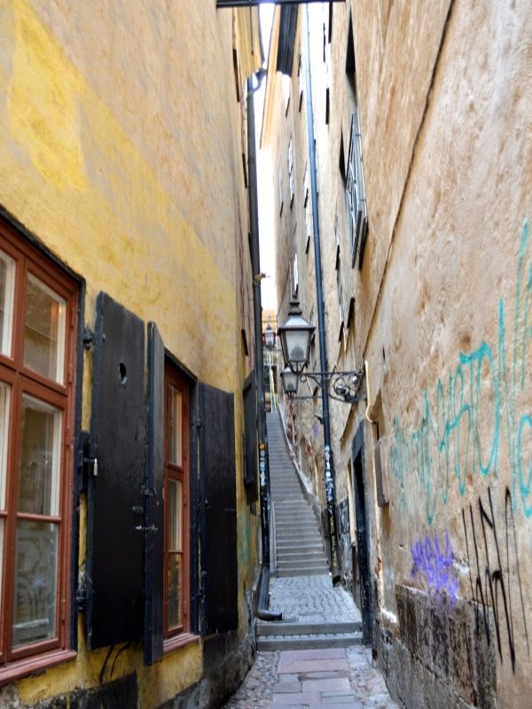 Gamla Stan Has Many Narrow Lane Ways. This Is A Typical One. Cobbled Walkway With Tall Building On Either Side Dating Back To The 13th Century.