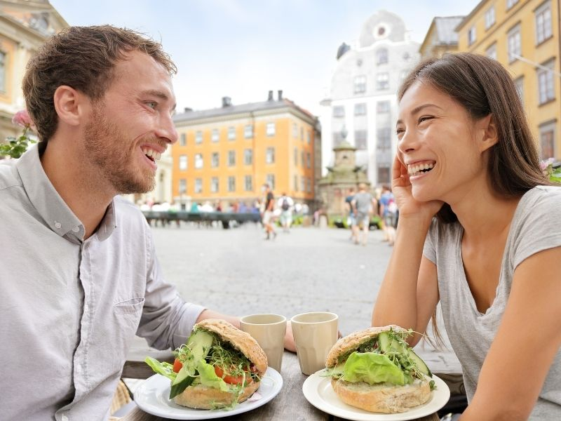 Young Couple Enjoying A Swedish Lunch In The Middle Of Stockholm.