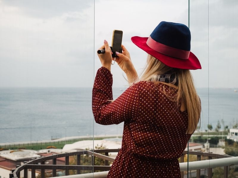 Female Checking Out The Ocean View From Her Hotel Room Booked On Booking.com.